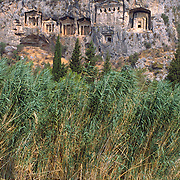 """Lycian tombs (or necropoli) from about 400 BCE can be seen by boat on the Dalyan Çay? River, above the ancient harbor city of Caunos, on the Turquoise Coast, near the town of Koycegiz, in southwest Turkey. Dalyan means """"fishing weir"""" in Turkish. The Dalyan Delta, with a long, golden sandy beach at its mouth, is a nature conservation area and a refuge for sea turtles (Caretta caretta) and blue crabs. Image published in the travel handbook """"Moon Istanbul & the Turkish Coast"""" by Jessica Tamtürk, Avalon Travel Publishing, 2010."""
