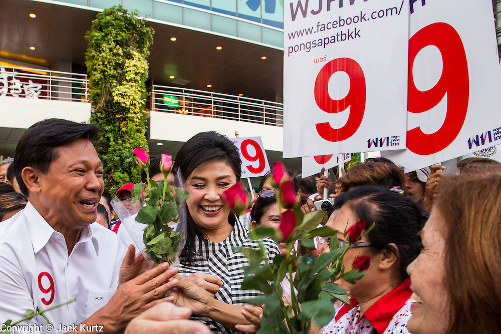 27 FEBRUARY 2013 - BANGKOK, THAILAND:  Pol Gen PONGSAPAT PONGCHAREON (left) and YINGLUCK SHINAWATRA, Prime Minister of Thailand, campaign for Pongsapat's election to Governor of Bangkok. Police General Pongsapat Pongcharoen (retired), a former deputy national police chief who also served as secretary-general of the Narcotics Control Board is the Pheu Thai Party candidate in the upcoming Bangkok governor's election. (He resigned from the police force to run for Governor.) Former Prime Minister Thaksin Shinawatra reportedly personally recruited Pongsapat. Most of Thailand's reputable polls have reported that Pongsapat is leading in the race and likely to defeat Sukhumbhand Paribatra, the Thai Democrats' candidate and incumbent. The loss of Bangkok would be a serious blow to the Democrats, whose base is the Bangkok area.    PHOTO BY JACK KURTZ