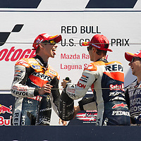 Repsol Honda riders Casey Stoner and Dani Pedrosa celebrate with Yamaha Factory rider Jorge Lorenzo on the podium of the U.S. MotoGP race at Mazda Raceway Laguna Seca, Sunday, July 29, 2012.