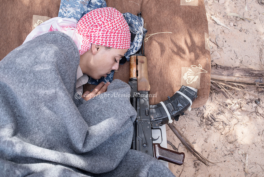 Libya: A Libya's Government of National Accord's (GNA) fighter sleeps after a night of fighting on the frontline with ISIS in Sirte. Alessio Romenzi