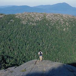 Weld, ME. A hiker stands on a ledge near the east peak of Tumbledown Mountain. Mt. Blue is in the distance. Northern Forest.