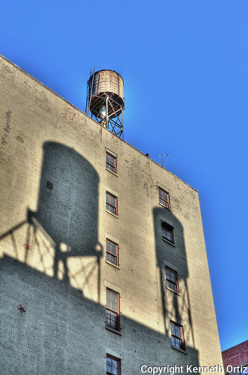 A water tower on top of a building with two water tower shadows projected on the side of the building.