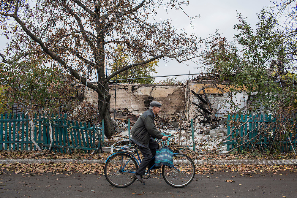 A man rides a bicycle in the Kievsky district, where pro-Russia rebels coordinate fighting to gain control of the Donetsk airport on Friday, October 17, 2014 in Donetsk, Ukraine. Photo by Brendan Hoffman, Freelance