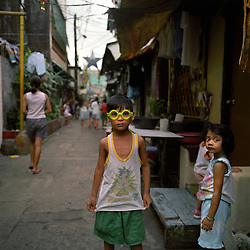 """A young boy stands in the main alley way of Leveriza Malate, a slum area where Teresita """"Tita"""" and Demetrio Comodaz """"Emmet"""" used to live in Manila, Philippines on Dec. 2006.  After years of Emmet working in Saudi Arabia, the couple now can afford to live in a nice house about an hour south of Manila, and rent their former shanty house to other families. However, the hard earned prosperity comes with a hefty price for many Filipino workers, as many of them get sucked into gambling and alcoholism from the loneliness acquired from years abroad."""