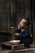 A boy enjoys his meal in a mountain village near Luang Prabang, Laos.