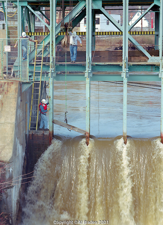Workers pulling the flash boards on Bellows Falls Dam, Bellows Falls, VT, during spring freshet.