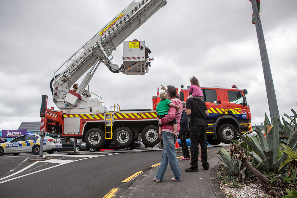 Police and firecrews used an aerial appliance to secure, then take down a sign in Glenfield, damaged after severe gusts blew through Auckland, New Zealand, Saturday, November 30, 2013. Credit:SNPA / Bradley Ambrose