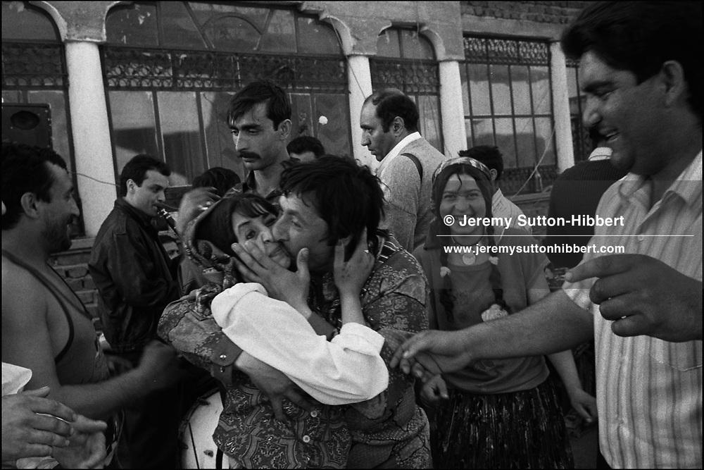 LIULIU GOGU MIHAI FORCIBLY KISSES CASINCA MIHAI DURING DANCING FOR ROMANIAN ORTHODOX EASTER CELEBRATIONS. SINTESTI, ROMANIA, MAY 1997..©JEREMY SUTTON-HIBBERT 2000..TEL./FAX. +44-141-649-2912..TEL. +44-7831-138817.