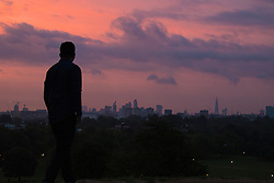 Primrose Hill, London, September 22nd 2016. A man admires the city skyline on Primrose Hill as the autumn equinox sun rises over London . &copy;Paul Davey<br /> FOR LICENCING CONTACT: Paul Davey +44 (0) 7966 016 296 paul@pauldaveycreative.co.uk