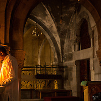 Israel, Jerusalem, Man praying by light of candle inside gloomy interior of Church of Holy Sepulchre