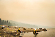 Smoke from the King Fire in the El Dorado National Forest casts a haze over contract fire crews dispatched to fill water tenders for fire engines in the French Meadows Resevoir. Due to severe drought the lake was at a fraction of it's capacity as the fire burned nearby. The tree stumps remain from when the trees were logged and the natural valley dammed and flooded as a water storage project.