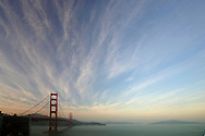 A view from the southern end of the Golden Gate Bridge in San Francisco, California with streaming clouds above.