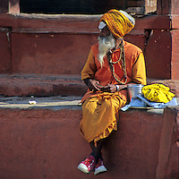 Asia, Nepal, Bhaktapur. A Sadhu in sneakers sits in Durban Square, Bhaktapur.