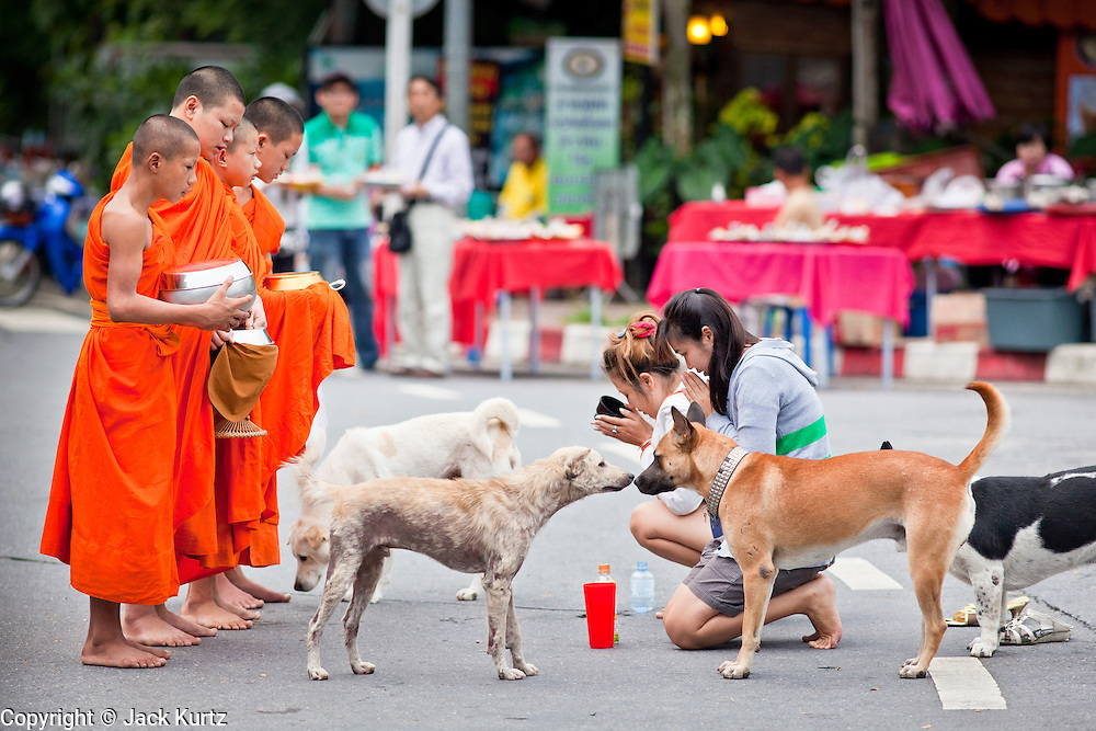 """28 JUNE 2011 - CHIANG MAI, THAILAND:  Buddhist monks on their morning alms rounds in Chiang Mai, Thailand. The monks go out every morning and solicit food from the people in the neighborhood. For the people who provide food and other supplies, it's a way to """"make merit"""" for the afterlife.  PHOTO BY JACK KURTZ"""