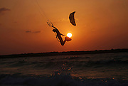 Kite surfing jump in the Mediterranean sea The surfer is passing the sun at sunset