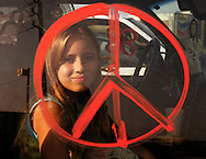 Jaycee Kane is framed by a peace symbol painted on her van in reference to Hurricane Rita as she takes a break from traffic in east Houston September 22, 2005. Lane and her family had been on the road 11 hours trying to evacuate before the storm arrives later in the week.