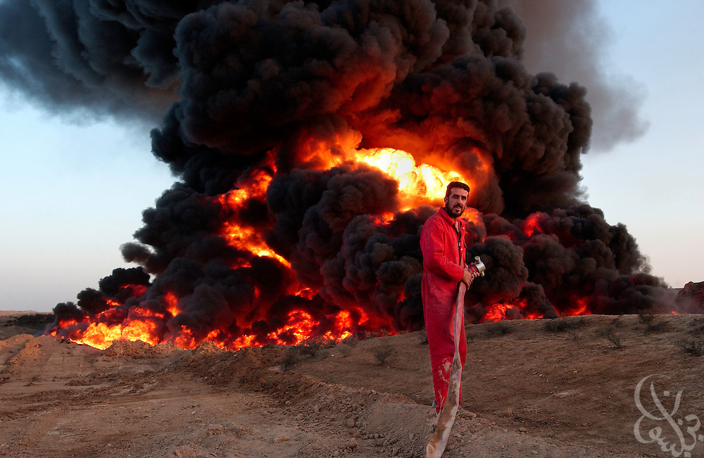 An Iraqi firemen waits for water to extinguish a section of ruptured Iraqi oil pipeline that has been burning for several days in the Northern Iraqi town of Ash Sharqat August 18, 2003.   The thousand kilometer Iraqi pipeline, which carries valueable oil exports northward to Turkey, often is the target of attacks.
