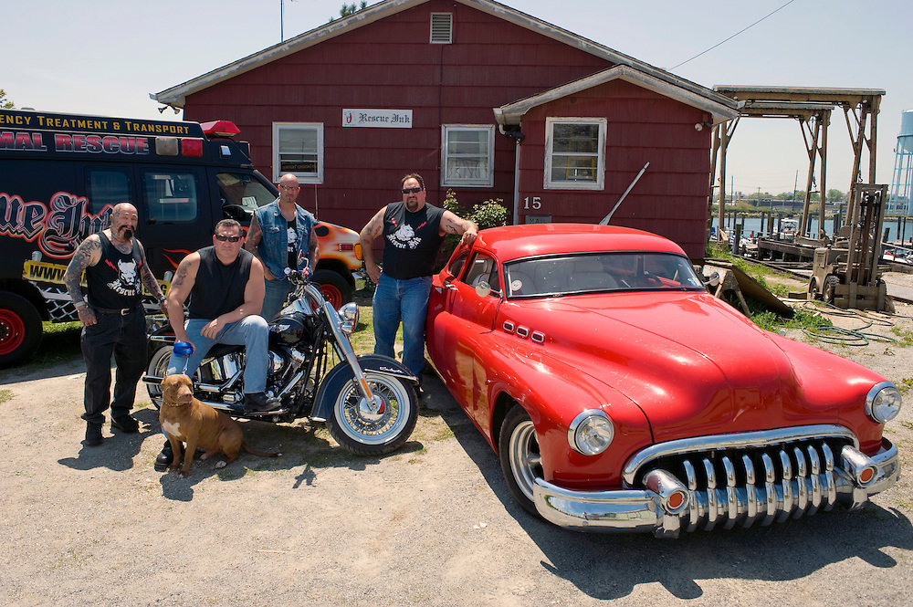 "Rescue Ink, Long Island, New York, taettowierte Motoradgang, Verein zur Rettung mishandelter Hunde und anderer Tierarten.vlnr (left to right):.""Batzo"", Joe Panz, Jonny ""O"", ""Big Ant"" mit Pitbull 'Rebel' vor dem Vereinshaus in Long Island..Rescue Ink rettete dem Pitbull 'Rebel' das Leben, er war in Virginia als Koeder fuer Kampfhunde eingesetzt worden und erlitt schwerste Verletzungen. ..Rescue Ink, the animal rescue group that brings an in your face approach to the fight against animal abuse and neglect. The goups members are heavily tattooed and ride motorbikes. Their pitbull 'Rebel', who lives at their headquarters, was rescued from a dog fighting operation, where he was used as bait. He was near death when two members of Rescue Ink flew to Virginia to save him...Foto © Stefan Falke."