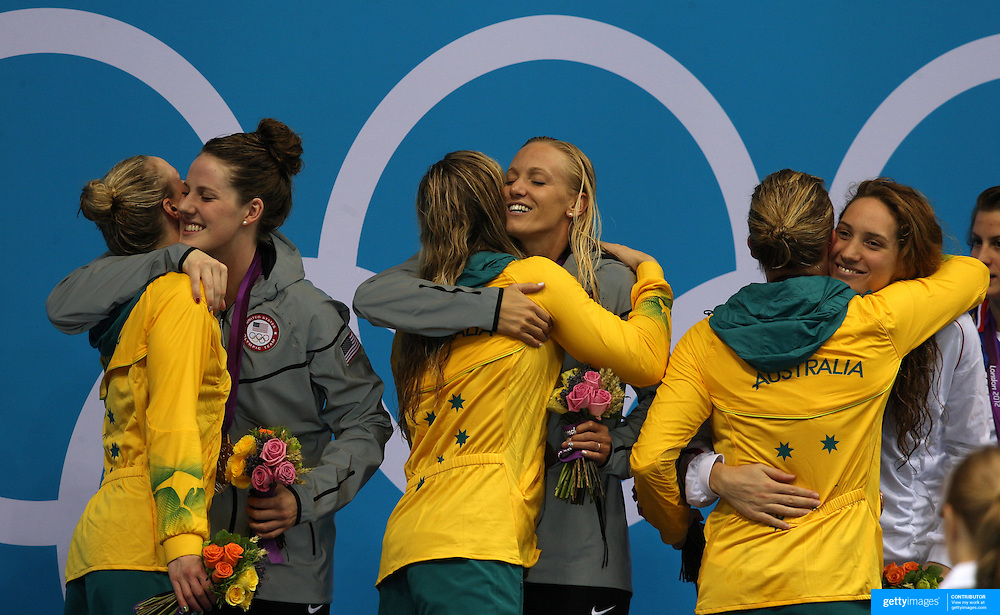 Synchronised hugs as USA, Australia and French swimmer hug after the medal presentation as The USA Women's 4 X 200m Freestyle relay team of Missy Franklin, Dana Vollmer, Shannon Vreeland and Allison Schmitt win the Gold medal at the Aquatic Centre at Olympic Park, Stratford during the London 2012 Olympic games. London, UK. 1st August 2012. Photo Tim Clayton