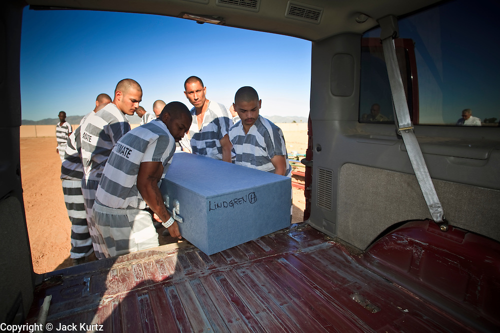 """18 MARCH 2010 - SURPRISE, AZ: Inmates on the """"Chain Gang"""" pull a casket out of the funeral home panel van during the interment of indigent county residents in White Tanks Cemetery on Camelback Rd. in an unincorporated part of the county near Surprise. The county spent about $2.5 million to inter indigent people in what is Maricopa County's """"potters field."""" About 3,000 people, children and adults, are buried in the dusty field west of Phoenix.      PHOTO BY JACK KURTZ"""