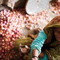 An elderly woman sits on the floor and sorts through onions to earn a small amount of money in the municipal market in Srimongol in the tea growing region of north east Bangladesh
