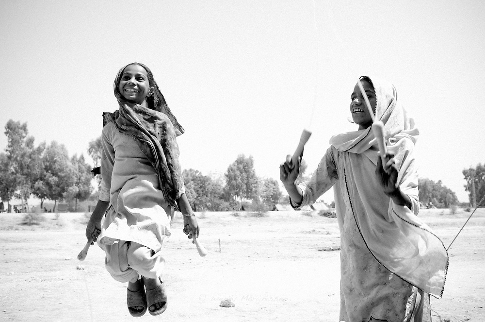 Two girls skip rope. In a school in the tent camp for flood victims, teachers try to continue giving some education and provide toys during play time to occupy the children. Sukkur, Paksitan, 2010