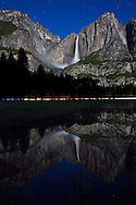 Lunar Rainbow also known as a moonbow, appears under moonlight over Yosemite Falls and reflected in a flooded Cook's Meadow - Yosemite National Park, California