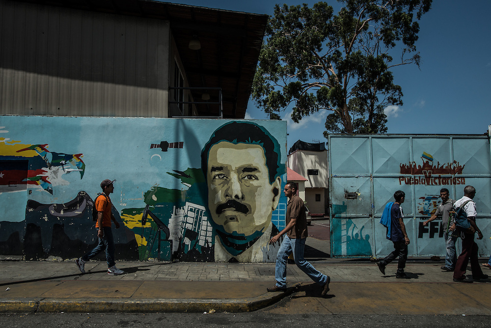 """CARACAS, VENEZUELA - MAY 20, 2016: People walk past a mural of President Nicholas Maduro in Caracas. Tensions came to a head last week when President Maduro went on television to criticize the Organization of American States, a  longtime ally of the socialists, which is now criticizing Venezuela's handling of the economic and political crises. Mr. Maduro took aim at Luis Almagro, its secretary-general, calling him a """"longtime traitor"""" and implying he was a spy.  Mr. Almagro responded with an open letter blasting the government. """"I am not a CIA agent,"""" the letter said. """"You betray your people and your supposed ideology with your tirades.""""  PHOTO: Meridith Kohut"""