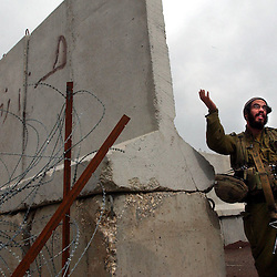 TZIPOREN, ISRAEL, MARCH 2:An Israeli soldier gestures to journalists next to the border with Lebanon near Tziporen army base in north Israel, Sunday, March 2, 2003 as Hezbollah Shiite militants watch from the other side of the fence.  .