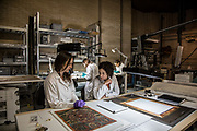 Rome, Vatican Museums, ethnological workshop (Chinese parchment, fabric and feathers). in the back from the left Stefania Passerin and Flavia Serena di Lapigioi paper art restorer. <br /> on the front deesk: Catherine Rivi&egrave;re painting art restorer and  Martina Brunori textil art restorer