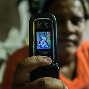 Maria (20) shows the picture of her daughter with microcephaly Eduarda Vitoria (5 months) and her other daughter inside their house, a shelter inside the slum of Santa Luzia in Recife, Pernambuco. Maria is unemployed and extremely poor. Maria used to work as prostitute and also was a crack addicted