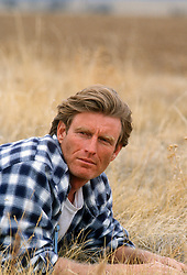 portrait of a handsome rugged man in tall grass on a ranch