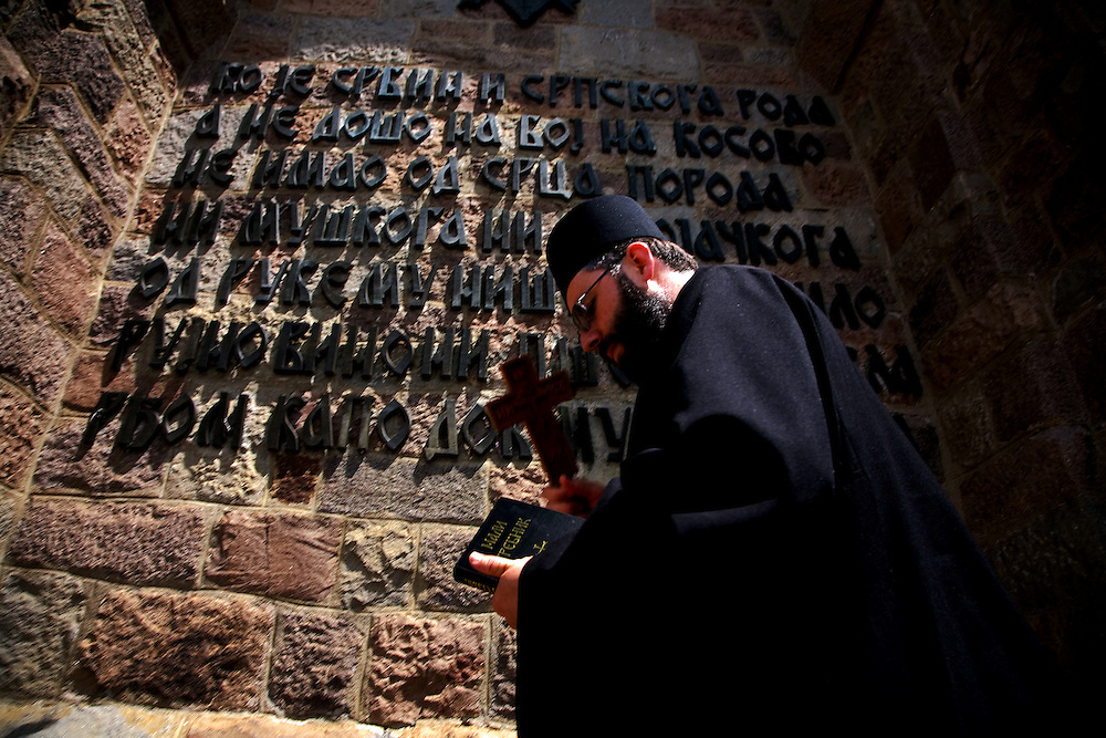 """Serbian orthodox priest kisses the wall of the memorial tower at Gazimestan, the site of the 1389 """"Battle of Kosovo""""...Gazimestan, Kosovo, Serbia."""