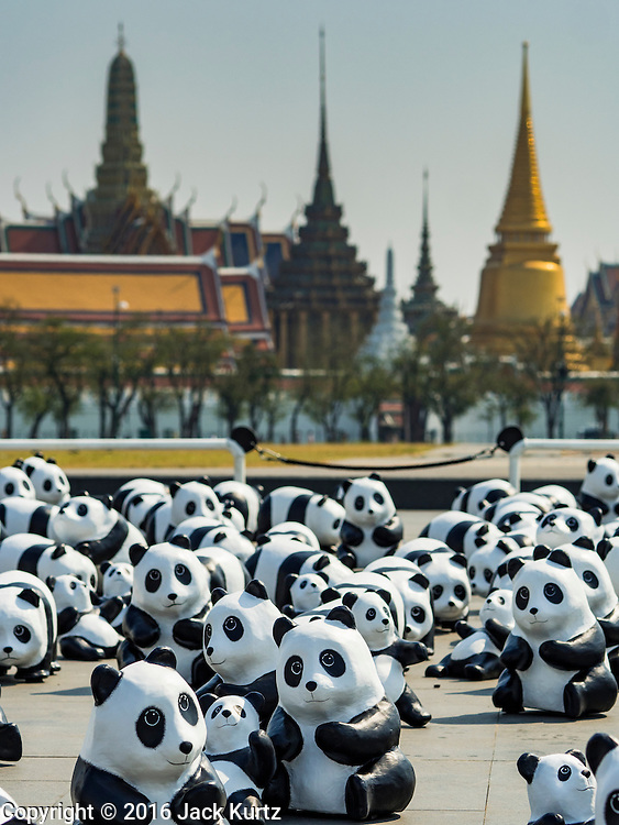 """04 MARCH 2016 - BANGKOK, THAILAND: The Grand Palace in the background behind the """"1600 Pandas+ World Tour in Thailand: For the World We Live In and the Ones We Love"""" exhibit on Sanam Luang in Bangkok. The 1600 paper maché pandas, an art installation by French artist Paulo Grangeon will travel across Bangkok and parts of central Thailand for the next week and then will be displayed at Central Embassy, a Bangkok shopping mall, until April 10. The display of pandas in Thailand is benefitting World Wide Fund for Nature - Thailand and is sponsored by Central Embassy with assistance from the Tourism Authority of Thailand and Bangkok Metropolitan Administration and curated by AllRightsReserved Ltd.     PHOTO BY JACK KURTZ"""