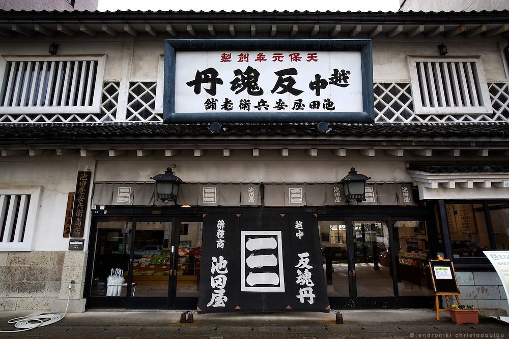 """TOYAMA MEDICINE.Front of IKEDAYA YASUBEI SHOTEN a traditional medicine shop in Toyama city.Ikedaya-Yasubei Shoten preserves the atmosphere of a time-honored herbal medicine shop. """"Ecchu-hangontan"""" written on the sign is said to be a miracle medicine that reinvigorates one's body. In the shop, visitors can watch a demonstration of making pills by using the traditional hand-operated pill maker. On the 2nd floor of the shop is the restaurant YAKUTO where healthy dishes made with Chinese herbal medicines are served. http://www.hangontan.co.jp/Toyama prefecture is located near the center of Japan and is approximatelythe same distance from the three largest cities in Japan-Tokyo,Nagoya,andOsaka. Toyama's pharmaceutical tradition has a more than 300 years history. As it is located on the Japan sea, it is facing China and has been an importer of traditional Chinese medicine knowledge which it developed through the years. There are now approximately 100 manufactures and over 100 factories in Toyama in terms of pharmaceutical products and Toyama prefecture acquires a steady reputation as Japan's medicine manufacturing base."""