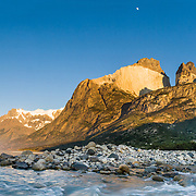 """At early sunrise under the Horns, a stream flows into Lago (Lake) Nordenskjold, at Albergue Los Cuernos, a refuge (hut) in Torres del Paine National Park, Chile, Patagonia, South America. The panorama was stitched from 5 overlapping images. Published in """"Light Travel: Photography on the Go"""" book by Tom Dempsey 2009, 2010."""
