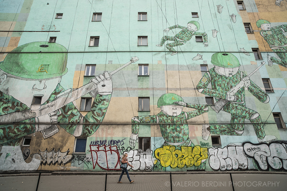 """""""Soldier Puppets"""" by street artist Blu, on Avenue of John Paul II. This large graffiti depicts puppet soldiers. On the helmets they have a Euro symbol that merges into a communist hammer and sickle. On the soldiers arms the SS Nazi takes the form of a double dollar $$. Whoever the enemy, Warsaw new generations still face the nightmares of their past."""