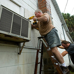 David Rogers (C) with his son Shawn cover up the windows to David's home in Cedar Key, Florda in preparation for Tropical Storm Alberto June 12, 2006. REUTERS/Scott Audette