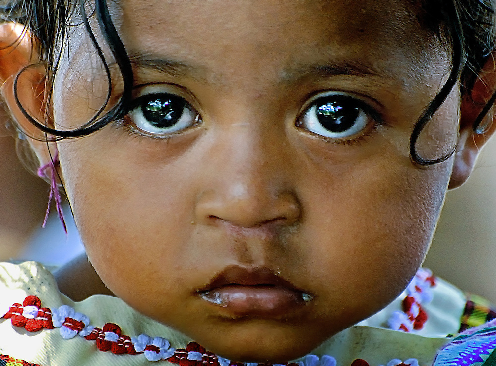 A young girl with large curls is dressed to attend a church service on Lembata Island, Indonesia.