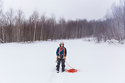 A woman organizes her climbing rope while winter camping in New Hampshire's White Mountains. Randolph Community Forest.