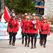 Royal Canadian Mounted Police, or RCMP officers in traditional dress red serge uniforms parade during the Canada Cup.  Whistler BC, Canada.