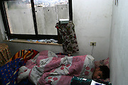 FOR STERN MAGAZINE-GERMANY OUT.Palestinian student Mohamed Qdimat sleeping in his bed in his apartment he shares with other students attending the Al Quds University along 8 meter high cement wall Israel is building to separate the east Jerusalem village of Abu Dis Jan,17,2004. Israel plans to dispute the World Court's right to rule on its huge barrier going up inside the West Bank. (Photo by Heidi Levine/Sipa Press).