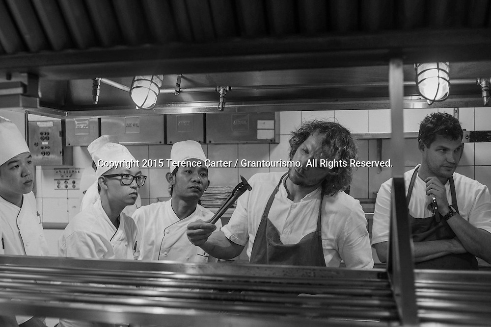 The Grand Gelinaz! Shuffle on July 9th 2015 Noma at Nahm, Bangkok<br /> <br /> The next day at 11:30am on the dot, and right on schedule, the Noma chefs started visiting each station to show the chefs exactly how they wanted the ingredients cooked and plated. Seeing the finished dishes for the first time, the Thai chefs watched, made notes and took photos to use as a reference. Here Chef Thomas shows the chefs on this &lsquo;hot&rsquo; station just how he wanted the baby corn cooked over coals. Copyright 2015 Terence Carter / Grantourismo. All Rights Reserved.