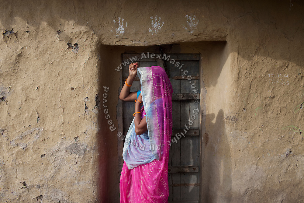 Malti Devi, 40, a housewife and the mother of Kanchan Kumari Sharma, 12, is covering her head with a pink sari while standing in front of their home in Sersiya Kekrahi village, Varanasi District, Uttar Pradesh, India. In 2012, Kanchan went with a friend to bring lunch to her father, around 2 km away from her home. On the way they met Rajesh (rapist) and Ashok, a friend of his. Both girls were picked up on the spot using an excuse. Ashok drove Kanchan's friend home, but Rajesh forced Kanchan to travel with him during six days and for hundreds of kilometres across different states. (Mirzapur / Chennai / Itarsi / Bhusawal) He raped her once behind the station in Itarsi. With great effort and some coincidence, the uncle of Kanchan managed to bring her back home. Although she was scared, she insisted on going to the police to file a case (FIR). She was kept at the police station for 12 days and threatened to prevent her from filing an official case. Ashok and Rajesh are from higher caste and wealthy families. While Rajesh spent 24 days in jail initially in summer 2012, he is now a free man while the trial is still going on. Kanchan's family is now struggling to put together 30.000 Indian Rupees (500 USD) to continue battling for justice in court.