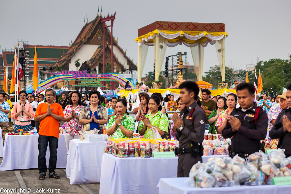 13 APRIL 2014 - BANGKOK, THAILAND:  People pray during a mass merit making ceremony for Songkran at Bangkok City Hall, Wat Suthat, one of the most important temples in Bangkok, is in the background. Many people go to temples and religious ceremonies to make merit on Songkran. Songkran is celebrated in Thailand as the traditional New Year's Day from 13 to 16 April. Songkran is in the hottest time of the year in Thailand, at the end of the dry season and provides an excuse for people to cool off in friendly water fights that take place throughout the country. Songkran has been a national holiday since 1940, when Thailand moved the first day of the year to January 1.   PHOTO BY JACK KURTZ