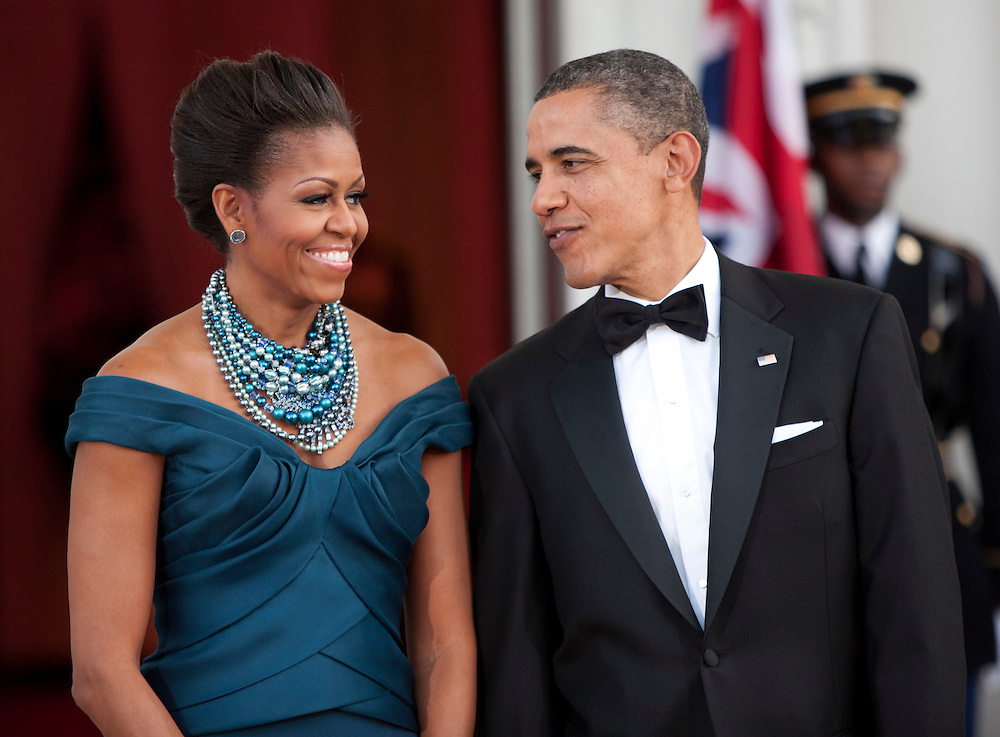 U.S. President Barack Obama and First Lady Michelle Obama wait to greet David Cameron, prime minister of Great Britain, and his wife Samantha arrive for a State Dinner at the White House in Washington, D.C., U.S., on Wednesday, March 14, 2012. Photographer: Joshua Roberts/Bloomberg