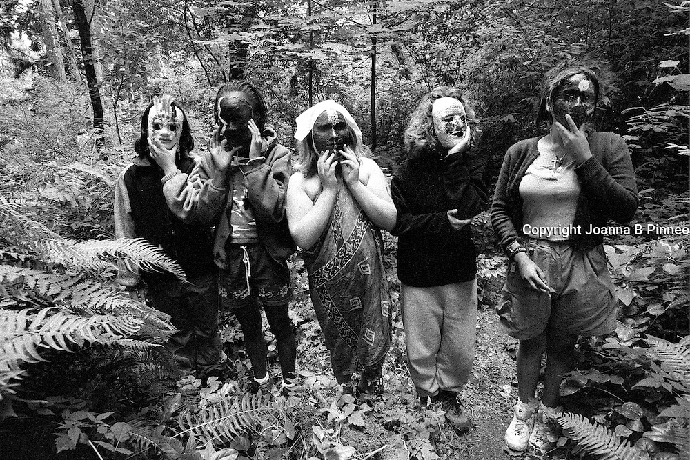 ©2001Joanna B. Pinneo All Rights Reserved.Baimbridge Island, Washington state.  Girls pose in their childhood masks in the forest on the Olympic Peninsula. They are on a Wilderness Coming of Age Journey organized by the Institute of Cultural Affairs  out of Bothell, Washington. Girls age 11-13 take a 3-week backpacking trip in the heart of the Olympic Peninsula and then participate in a 24-hour solo journey while camping out on the beach.