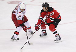 Feb 16; Newark, NJ, USA; New Jersey Devils center David Clarkson (23) takes the puck away from Carolina Hurricanes defenseman Joe Corvo (77) during the third period at the Prudential Center. The Devils defeated the Hurricanes 3-2.