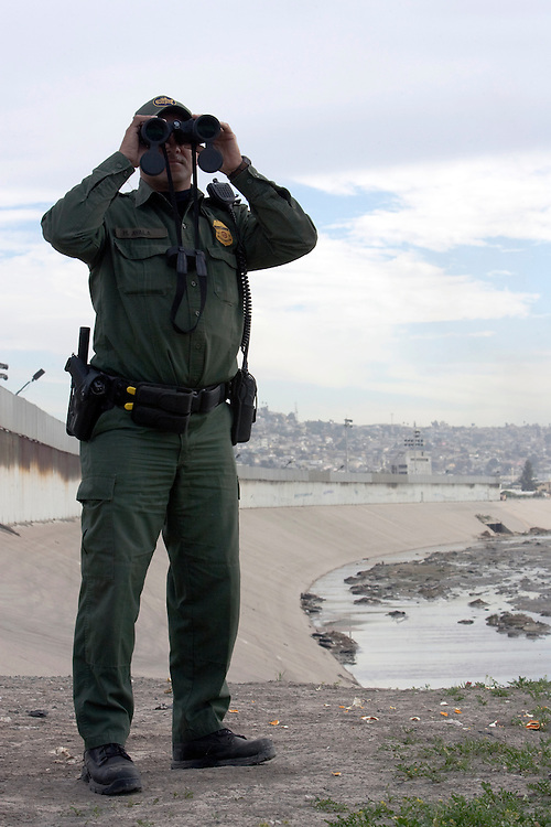 U.S. Border Patrol agents scan the border fence area that separates Tijuana, Mexico from San Diego, California for illegal entry. Please contact Todd Bigelow directly with your licensing requests.