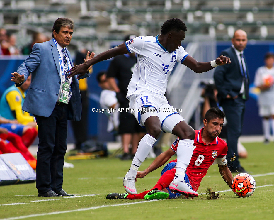 Honduras head coach Carlos Tábora, left, looks on as Honduras forward Alberth Josue Elis Martínez #17, center, moves the ball away from Costa Rica midfielder Luis Sequeira #8 in the first half of a CONCACAF men's Olympic qualifying soccer match in Carson, Calif., Sunday, Oct. 4, 2015. (AP Photo/Ringo H.W. Chiu)